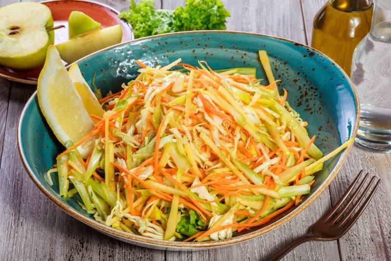 Salade fraîche avec la pomme, la carotte, le chou, le céleri et le citron sur la fin en bois de fond  Nourriture saine images libres de droits