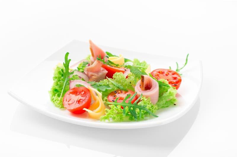 Salade fraîche avec les tomates, l'arugula, le fromage et le jambon du plat blanc et du fond blanc image stock