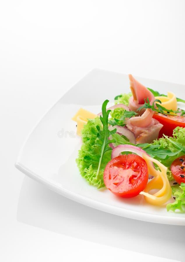 Salade fraîche avec les tomates, l'arugula, le fromage et le jambon du plat blanc et du fond blanc photo libre de droits