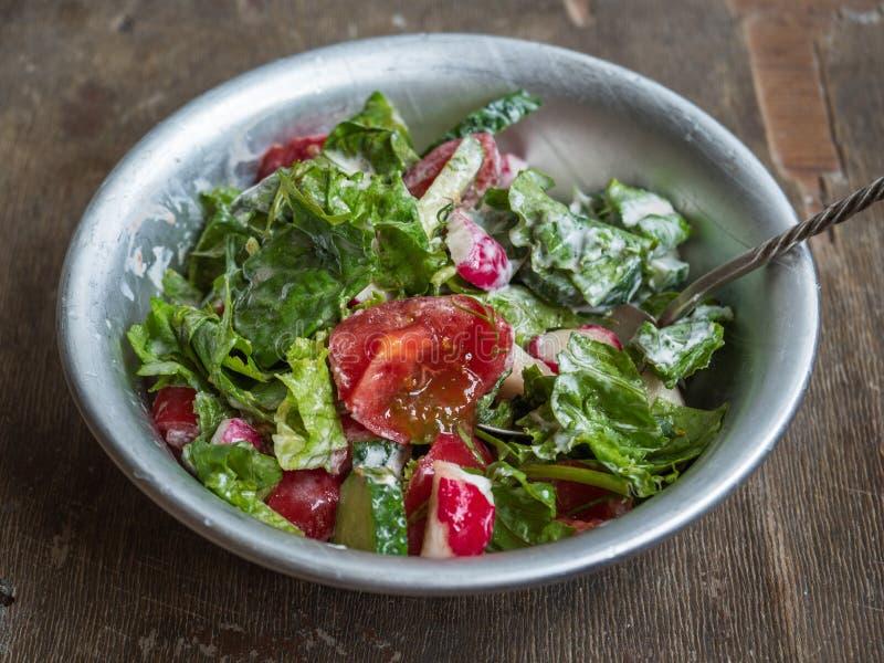 Salade fraîche d'été des tomates, des concombres et des herbes aromatiques dans une cuvette en aluminium profonde avec une cuillè image libre de droits