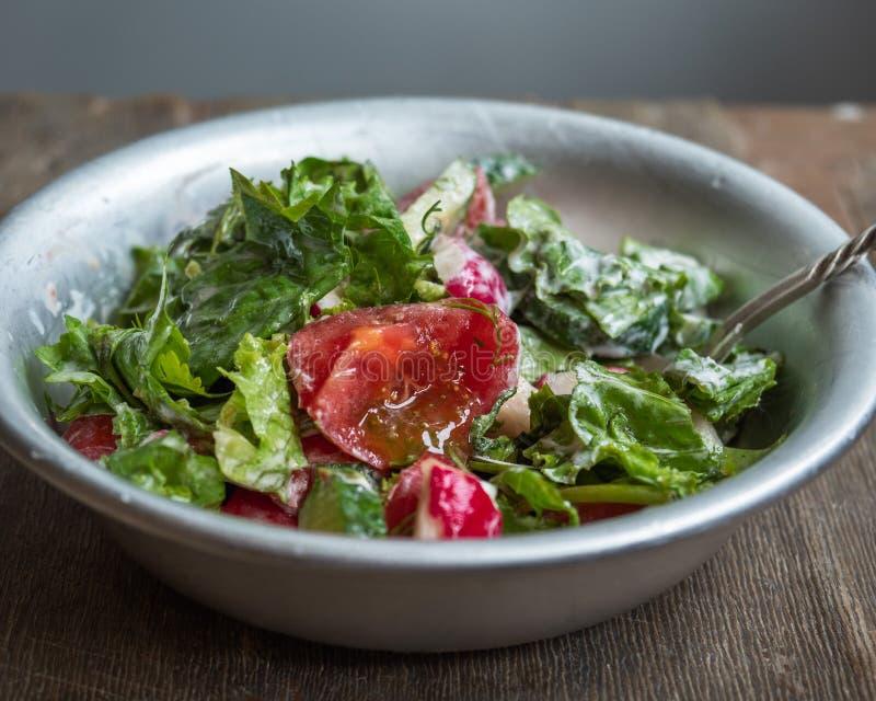 Salade fraîche d'été des tomates, concombres et herbes aromatiques, préparés avec la crème sure dans une cuvette en aluminium pro images stock