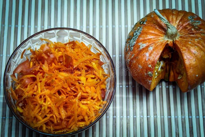 Salade fraîche de carottes râpées, citrouille, tomates tranchées et citrouille avec une tranche coupée sur une serviette en bambo images libres de droits