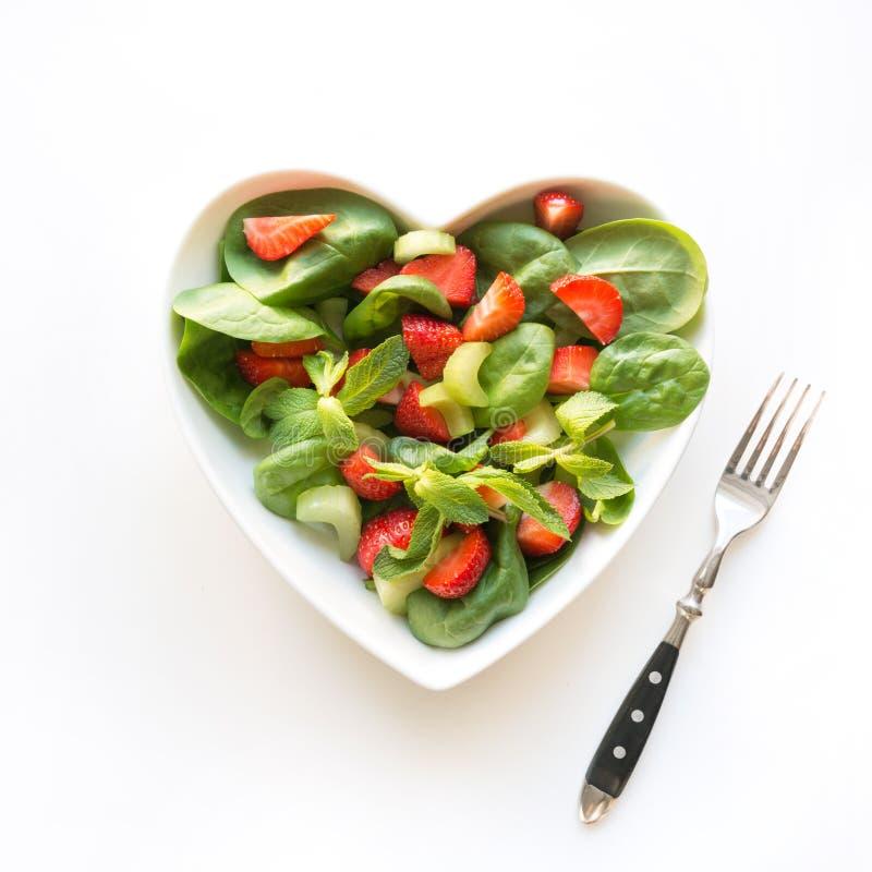 Salade fraîche de la fraise, céleri, épinards, pignons, fromage dans le plat comme coeur sur le blanc Image carr?e Consommation p images stock