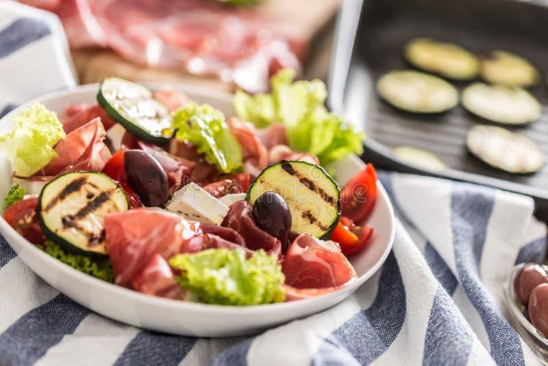 Salade fraîche de laitue avec les tomates d'olives de feta de jambon de Parme de Di de coppa de courgette et l'huile d'olive gril image libre de droits