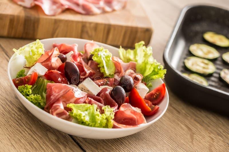 Salade fraîche de laitue avec les tomates d'olives de feta de jambon de Parme de Di de coppa de courgette et l'huile d'olive gril photographie stock