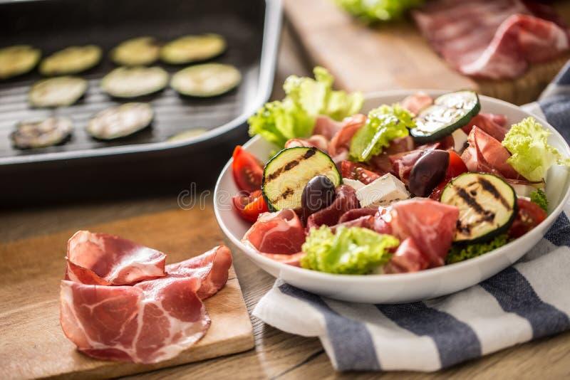 Salade fraîche de laitue avec les tomates d'olives de feta de jambon de Parme de Di de coppa de courgette et l'huile d'olive gril photo libre de droits