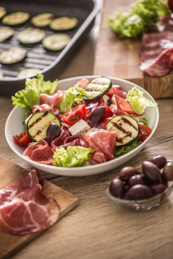 Salade fraîche de laitue avec les tomates d'olives de feta de jambon de Parme de Di de coppa de courgette et l'huile d'olive gril photo stock