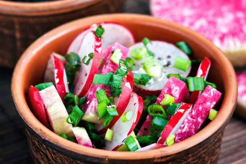Salade fraîche de radis avec les légumes et les oignons verts saisonniers assortis dans la cuvette brune sur la table en bois Pla photos libres de droits