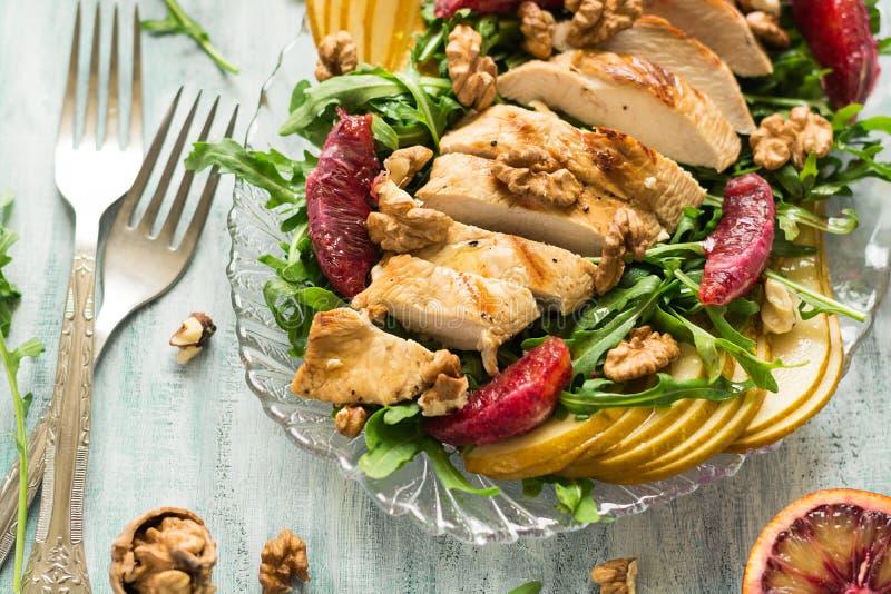 Salade fraîche de ressort avec du blanc de poulet grillé, arugula, poire et tranches et noix oranges photo stock