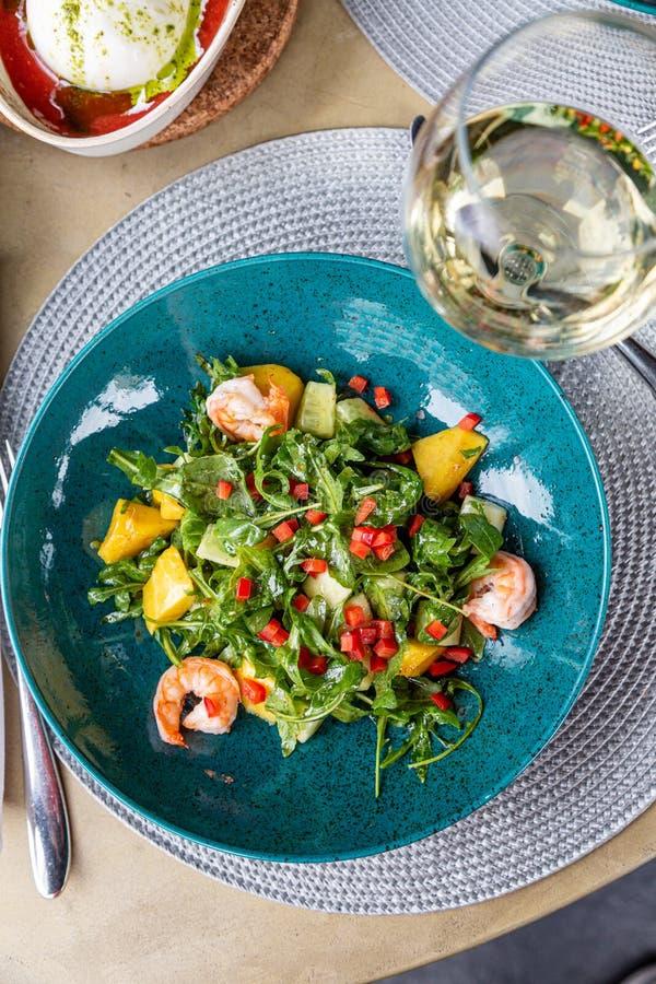 Salade fraîche et savoureuse fantastique avec des crevettes sur la table dans un beau plat avec un verre de vin Nourriture saine, photo stock