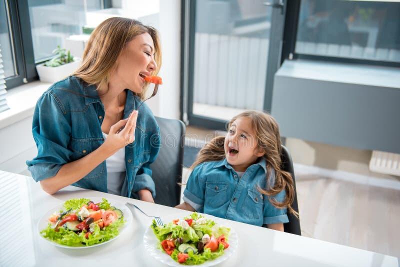 Salade gaie d'échantillon de famille dans la cuisine photos stock
