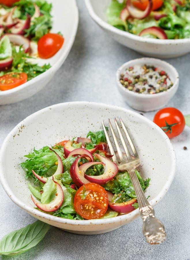 Salade gastronome légère avec de la laitue, des tomates-cerises et des oignons rouges photo stock
