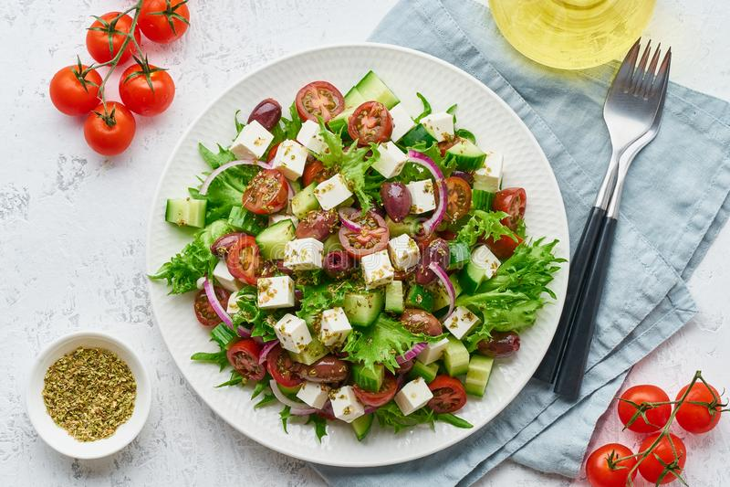 Salade grecque avec du feta et les tomates, nourriture suivante un régime sur la vue supérieure de fond blanc photos stock