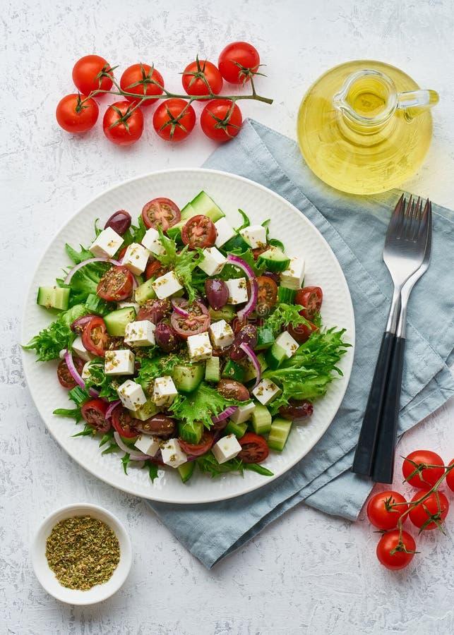 Salade grecque avec du feta et les tomates, nourriture suivante un régime sur la vue supérieure verticale de fond blanc image stock