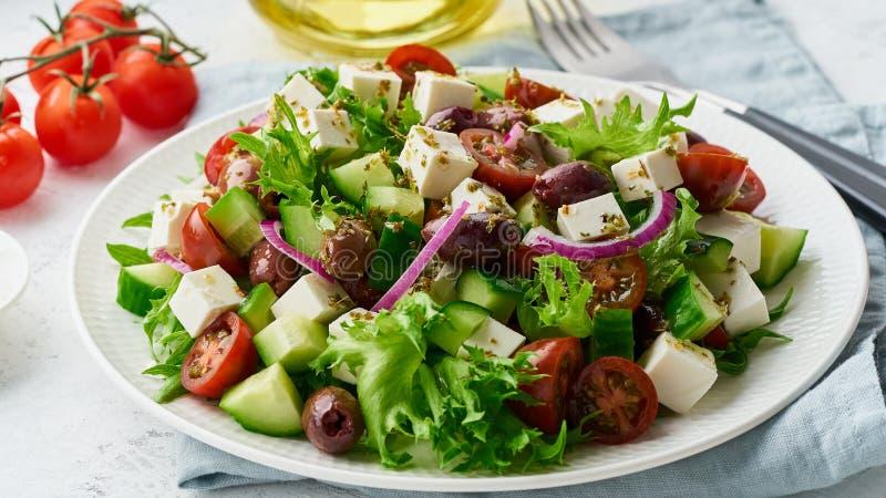 Salade grecque avec du feta et les tomates, nourriture suivante un régime sur le plan rapproché blanc de fond photo stock