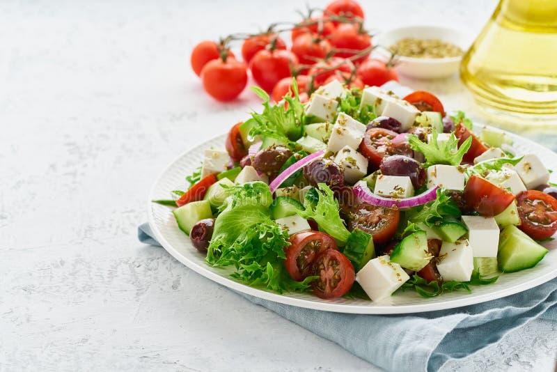 Salade grecque avec du feta et les tomates, nourriture suivante un régime sur le plan rapproché blanc de l'espace de copie de fon photographie stock libre de droits