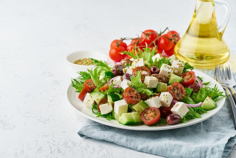 Salade grecque avec du feta et les tomates, nourriture suivante un régime sur le plan rapproché blanc de l'espace de copie de fon photo stock