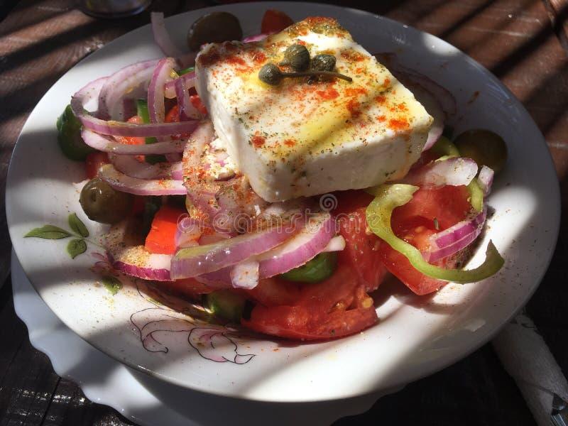 Salade grecque avec du feta, oignons rouges, tomates, origan, huile vierge supplémentaire image stock