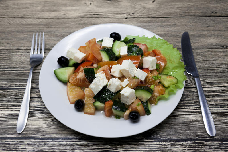 Salade grecque d'un plat blanc avec la fourchette et de couteau sur une table en bois Peut être employé comme photo pour des menu photos stock