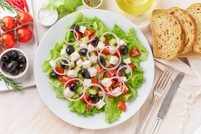 Salade grecque du plat blanc sur la vieille table en bois blanche rustique, salade fraîche avec des tomates, concombres, feta, oi photo libre de droits