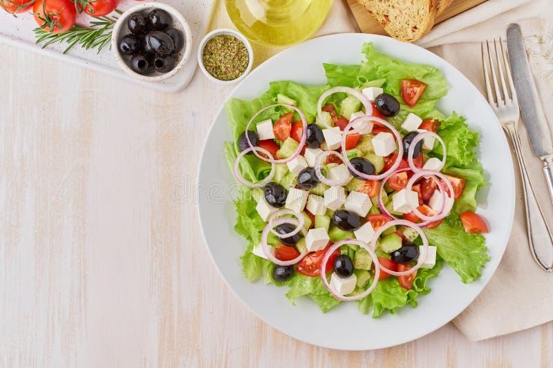 Salade grecque du plat blanc sur la vieille table en bois blanche rustique, salade fraîche avec des tomates, concombres, feta, oi photos stock