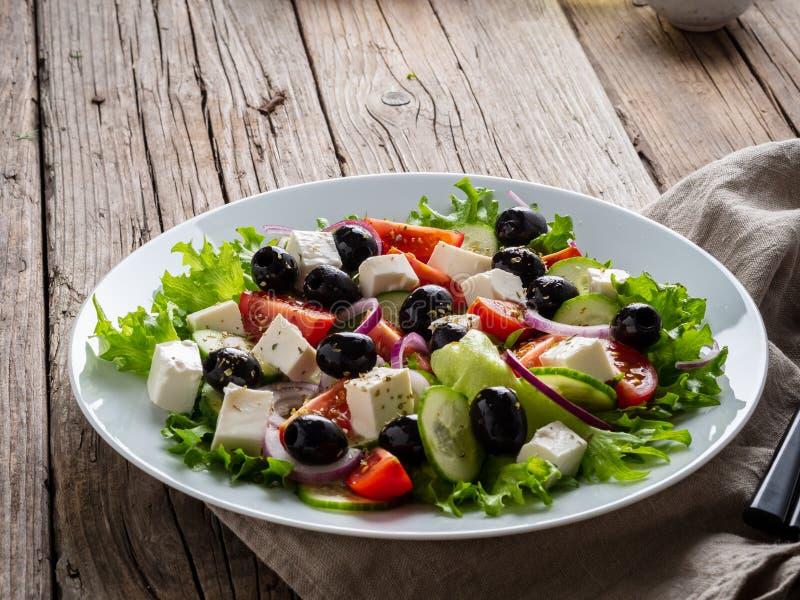 Salade grecque du plat blanc sur la vieille table en bois rustique, vue de côté, l'espace de copie images libres de droits