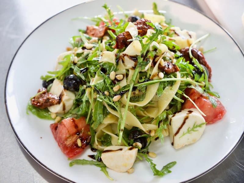 Salade italienne avec les macaronis, le fromage, la tomate et les herbes du plat blanc photo libre de droits