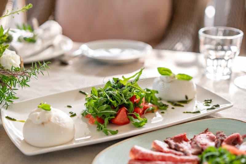 Salade italienne de Caprese le fromage de burrata, les tomates et l'herbe de basilic part Vinaigre balsamique disposé du plat bla photo libre de droits