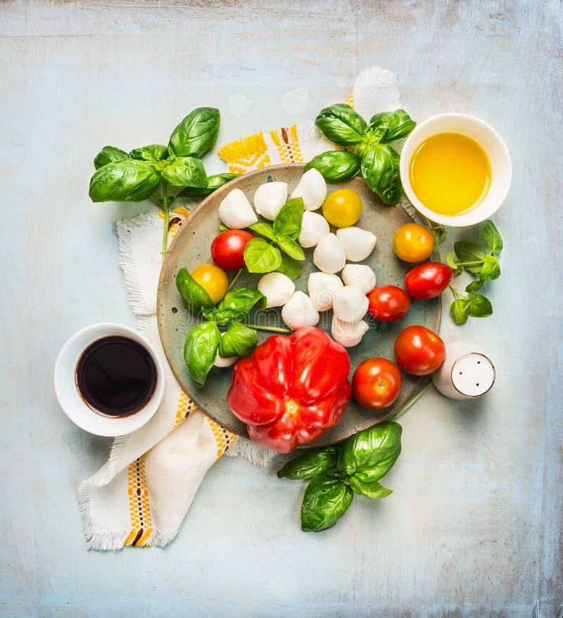 Salade italienne de tomates de mozarella, ingrediets avec de l'huile et vinaigre balsamique sur le fond en bois rustique photographie stock