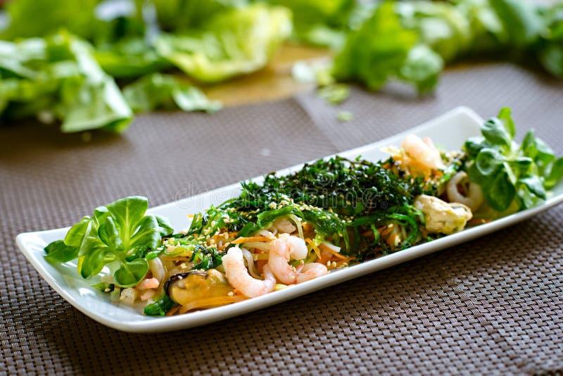 Salade japonaise saine avec les fruits de mer, l'algue et les graines de sésame dans le plat blanc photo stock