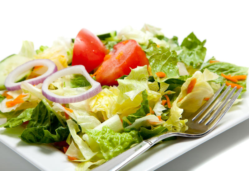 Salade jetée en l'air d'une plaque avec une fourchette photo libre de droits