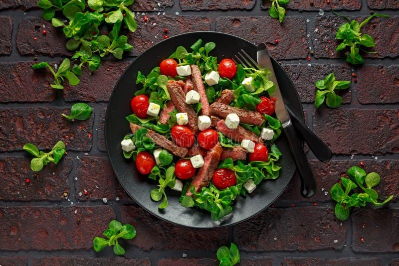 Salade juteuse de bifteck d'aloyau de boeuf avec les tomates rôties, le feta et les légumes verts dans un plat noir Nourriture sa image libre de droits