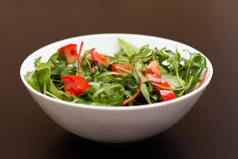 Salade légère avec des tomates dans la cuvette blanche de porcelaine images stock