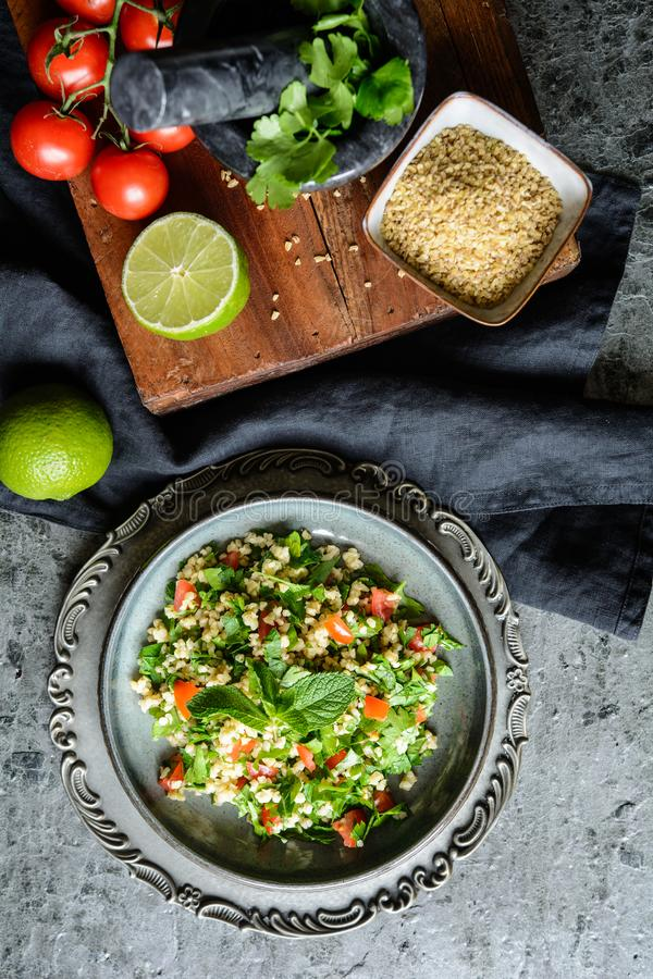 Salade libanaise de taboulé avec le bulgur, le persil, la menthe, les tomates et l'assaisonnement photos stock