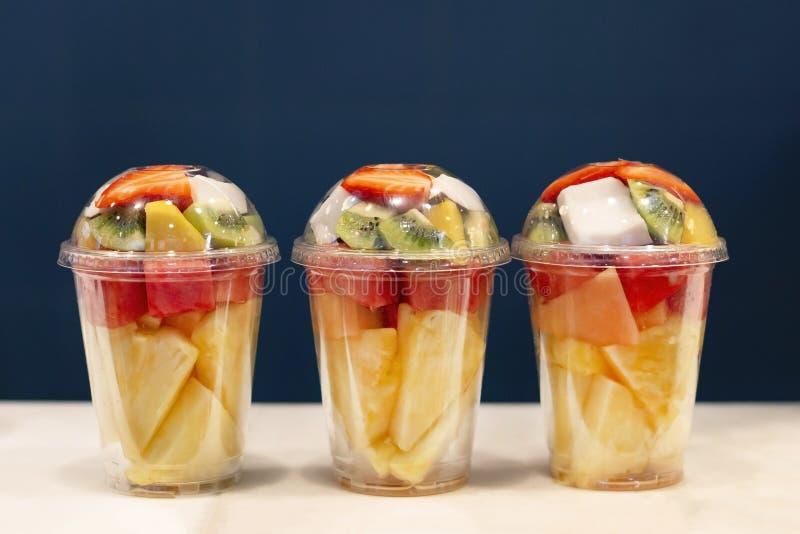 Salade mélangée de vitamine du fruit trois dans le verre en plastique prêt au traiteur Kiwi, ananas, pastèque, noix de coco, frai photo libre de droits