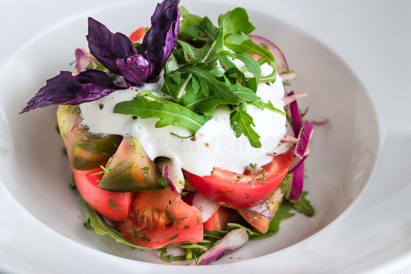 Salade met arugula, tomaten, uien, kalfsvlees, bieten Bruine tafelkleed, vork en lepel, voedselsamenstelling op de donkere houten stock afbeelding