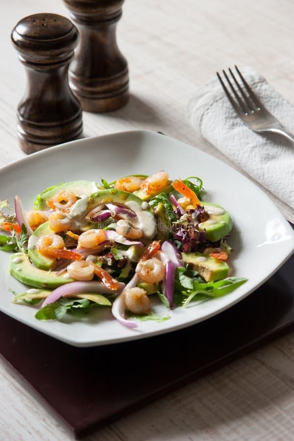 Salade met avocado en garnalen op de ceramische plaat met zout en peperschudbeker royalty-vrije stock afbeelding