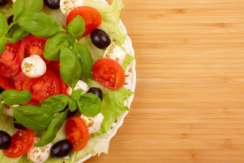 Salade met basilicum, mozarella, olijven en tomaat stock afbeelding
