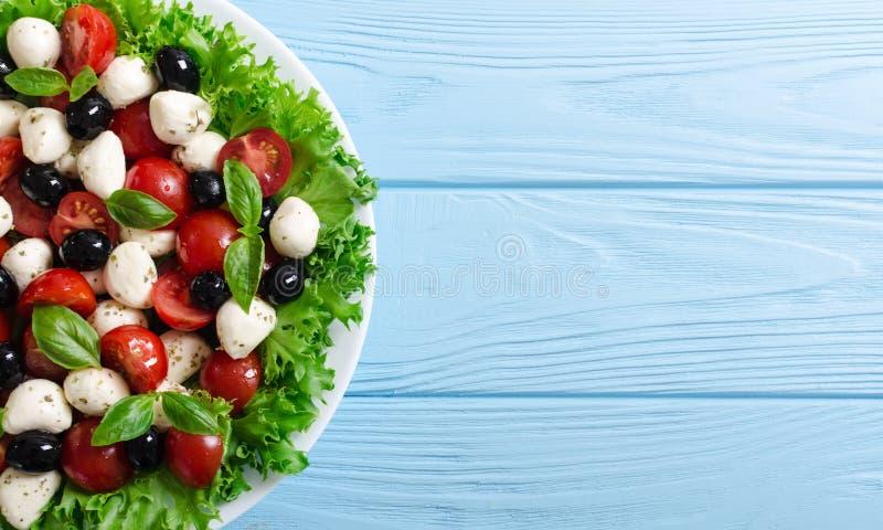 Salade met basilicum, tomaten, olijven en mozarella stock foto's