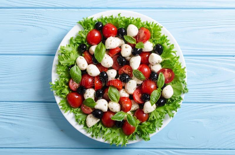 Salade met basilicum, tomaten, olijven en mozarella royalty-vrije stock afbeelding