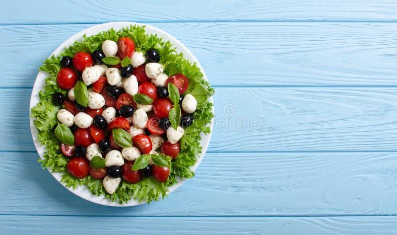 Salade met basilicum, tomaten, olijven en mozarella royalty-vrije stock foto's
