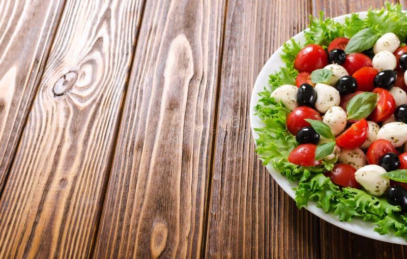 Salade met basilicum, tomaten, olijven en mozarella stock afbeeldingen
