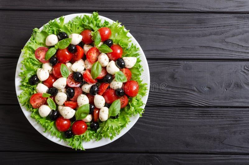 Salade met basilicum, tomaten, olijven en mozarella royalty-vrije stock afbeeldingen