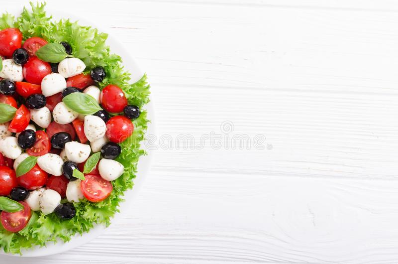 Salade met basilicum, tomaten, olijven en mozarella stock foto