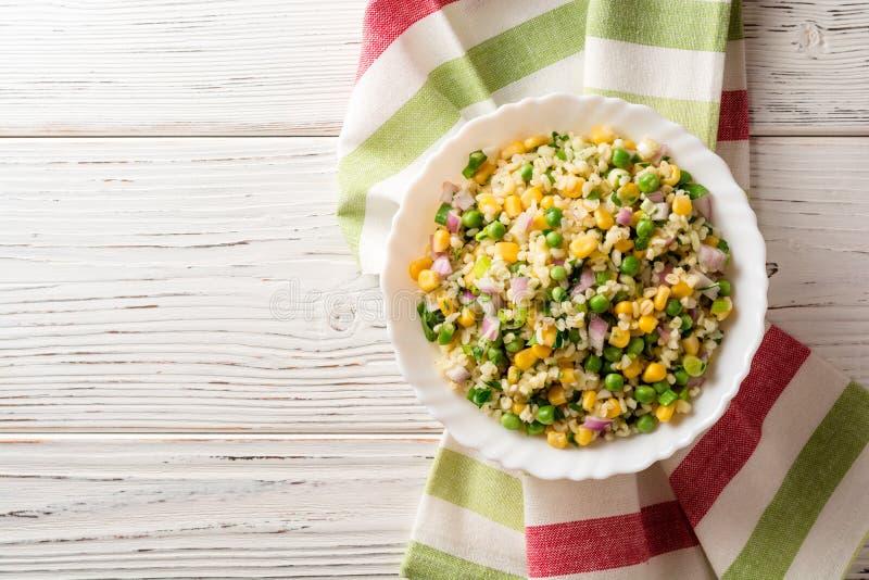 Salade met bulgur, groene erwten, graan, ui en greens op witte rustieke houten lijst tabbouleh stock afbeeldingen