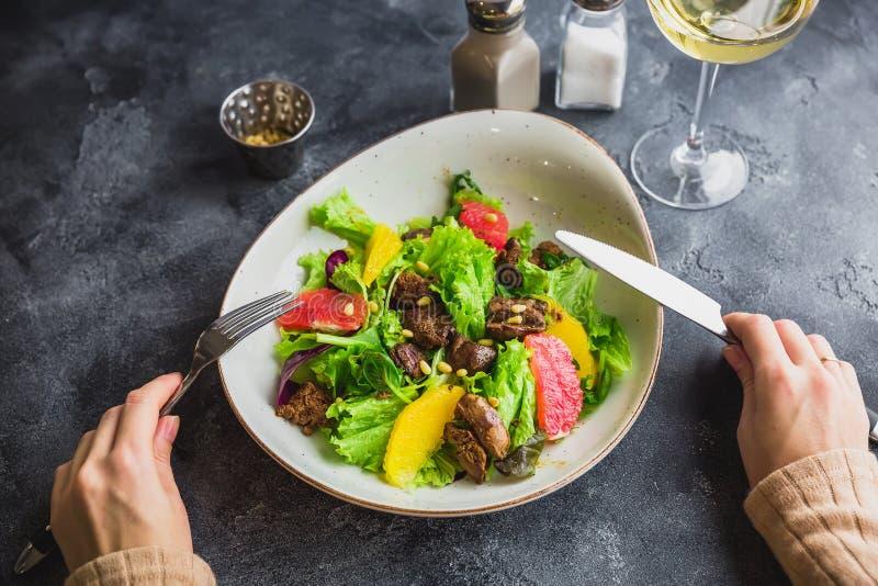 Salade met citrusvrucht, sla en geroosterde kippenlever in een plaat en een vrouwelijke hand stock afbeeldingen