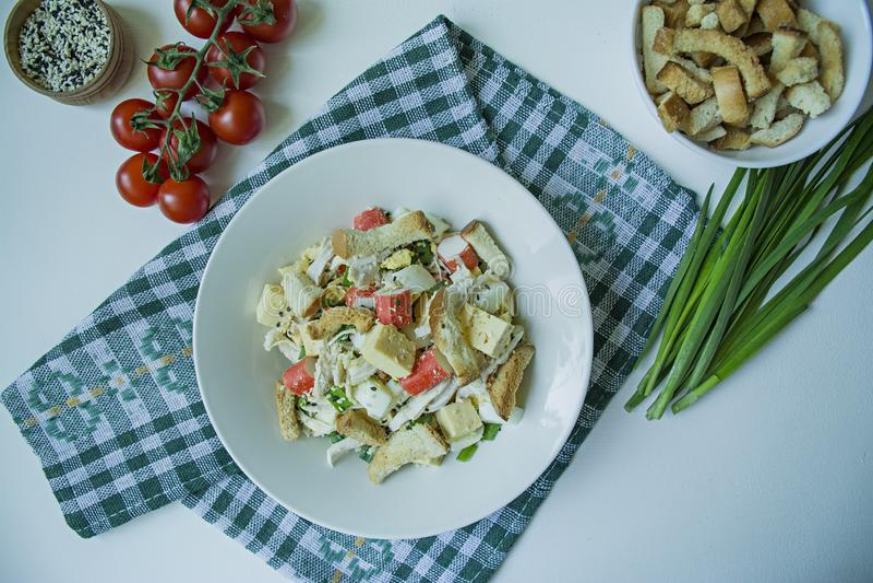 Salade met crackers, krabstokken, kippenfilet, verse kruiden en harde kaas die met olijfolie worden gekruid die in een witte plaa stock foto's