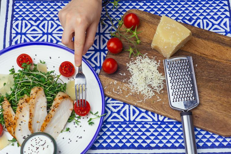 Salade met de salade van kippencaesar met micro-greens, kersentomaten en parmezaanse kaas op een blauwe ornamentachtergrond royalty-vrije stock afbeeldingen