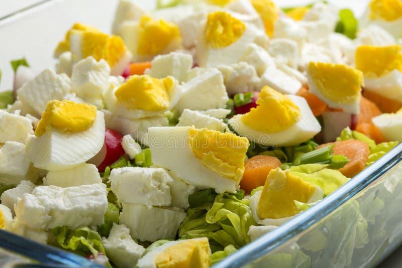 Salade met eieren, feta-kaas en wortel in glaskom stock fotografie