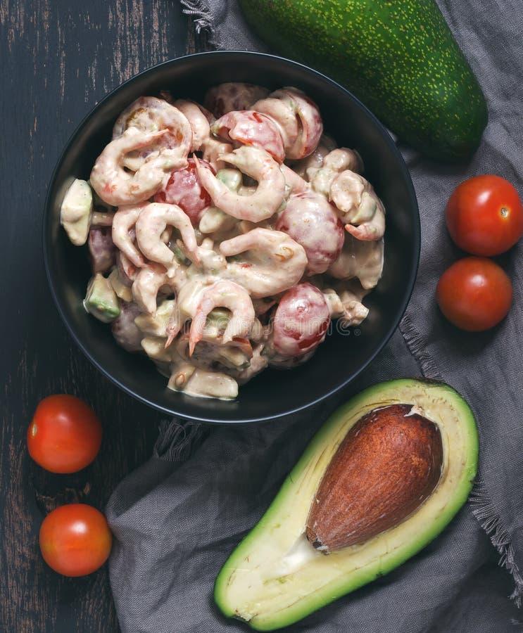 Salade met garnalen, avocado en tomatensaus in een zwarte schotel stock afbeeldingen